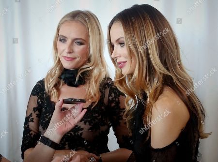 Marchesa designers Keren Craig, left, and Georgina Chapman listen to a reporter during an interview at the unveiling of the Marchesa bridal collection, in New York