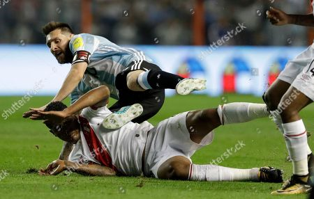 Argentina's Lionel Messi, top, is tackled by Peru's Wilder Cartagena during a World Cup qualifying soccer match at La Bombonera stadium in Buenos Aires, Argentina