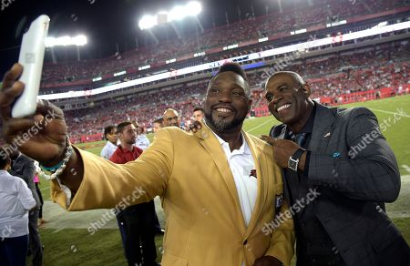 Former Tampa Bay Buccaneers' Warren Sapp, left, takes a photo with Deion Sanders before an NFL football game between the Tampa Bay Buccaneers and the New England Patriots, in Tampa, Fla