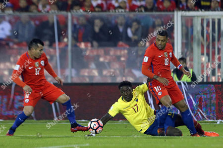Ecuador's Roberto Ordonez, center, fights for the ball against Chile's Gonzalo Jara, right, and Chile's Gary Medel during a 2018 World Cup qualifying soccer match in Santiago, Chile