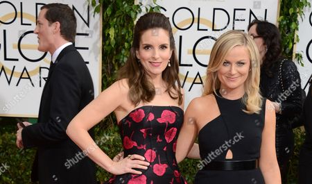 Tina Fey, left, and Amy Poehler arrive at the 71st annual Golden Globe Awards at the Beverly Hilton Hotel, in Beverly Hills, Calif. The producer of the Golden Globes and the Hollywood Foreign Press Association say they won't address the Sony hack during the big show, but the subject is fair game for hosts Fey and Poehler. 'I think that especially in the last couple of months, the girls have been provided with quite some interesting fodder,'? HFPA president Theo Kingma said coyly outside the Beverly Hilton's International Ballroom, where the ceremony will be held