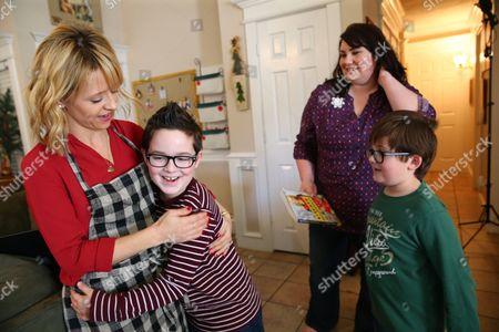 Stock Picture of Celebrity Chef Kelsey Nixon gets a hug from Brigham Tillotson as his mother Kelly and brother Oliver look on at Nature's Harvest bread's Kitchen Crash, in Forney, TX