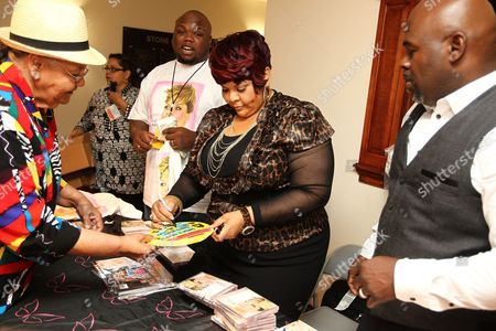 Actor David Mann right, looks on as his wife, gospel vocalist/actress Tamela Mann center, signs autographs after performing at the 2013 McDonald's Inspiration Celebration Gospel Tour, on Thursday, May, 9, 2013 in Fort Washington, MD