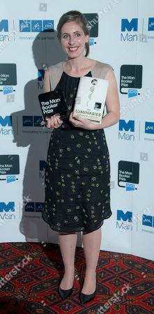 New Zealand author Eleanor Catton, who wrote her prize winning book, The Luminaries, poses for photographs with the Man Booker Prize for Fiction award at London's Guildhall