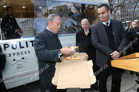 New York City Mayor Michael Bloomberg, left, is served the first Neapolitan Express pizza by T. Boone Pickens, center, and Max Crespo, Founder of Neapolitan Express, at the unveiling of Neapolitan Express, the first mobile food truck fully-powered by compressed natural gas, at City Hall Park in New York