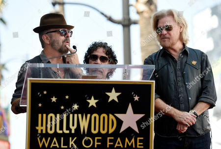 Musician Dave Stewart, left, addresses the crowd as pop music duo John Oates, center, and Daryl Hall look on during a ceremony to award Hall and Oates a star on the Hollywood Walk of Fame, in Los Angeles