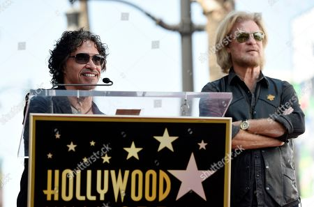 John Oates, left, addresses the crowd as his musical partner Daryl Hall looks on during a ceremony to award them a star on the Hollywood Walk of Fame, in Los Angeles