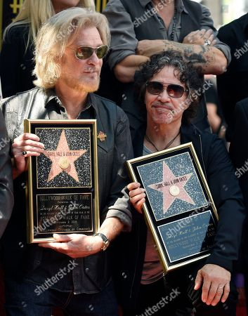 Pop music duo Daryl Hall, left, and John Oates pose together during a ceremony to award them a star on the Hollywood Walk of Fame, in Los Angeles
