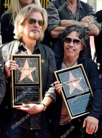 Pop music duo Daryl Hall, left, and John Oates pose together after receiving a star on the Hollywood Walk of Fame, in Los Angeles