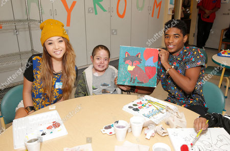 Chloe Jordache, and Nadji Jeter show off a patient's completed painting at Starlight Children's Foundation's Fun Center dedication at Childrens Hospital Los Angeles, in Los Angeles
