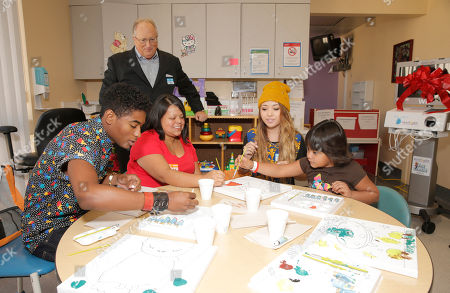 Aaron Brother's President Jim King watches as Nadji Jeter (left) and Chloe Jordache (yellow hat) paint with and a patient and her mother attend Starlight Children's Foundation's Fun Center dedication at Childrens Hospital Los Angeles, in Los Angeles