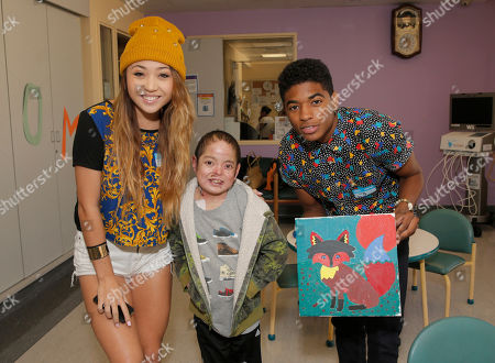 Chloe Jordache, and Nadji Jeter (right) show off a patient's completed painting at Starlight Children's Foundation's Fun Center dedication at Childrens Hospital Los Angeles, in Los Angeles