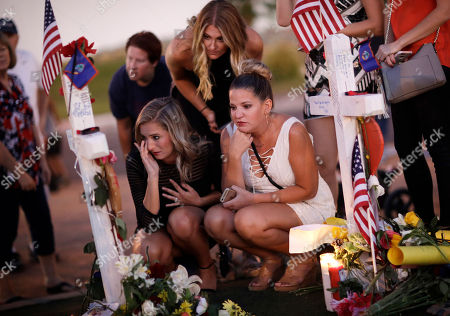 From left, Rachel Shepherd, Jamie Lambert and Annie Leach visit a makeshift memorial for victims of a mass shooting, in Las Vegas. Stephen Paddock opened fire on an outdoor country music concert on Sunday killing dozens and injuring hundreds