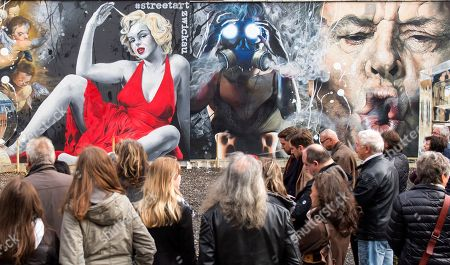 Visitors stand in front of a graffito wall painting showing Hollywood stas Marilyn Monroe and Jack Nicholson, right, by German street art artist TASSO (Jens Mueller) in Zwickau, eastern Germany, . TASSO created his art on different places all over the world