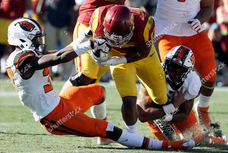 Vavae Malepeai, Kee Whetzel, Doug Taumoelau. Southern California running back Vavae Malepeai, center, gets the ball pulled on by Oregon State linebacker Kee Whetzel, left, as linebacker Doug Taumoelau, right, grabs a leg during the second half of an NCAA college football game in Los Angeles