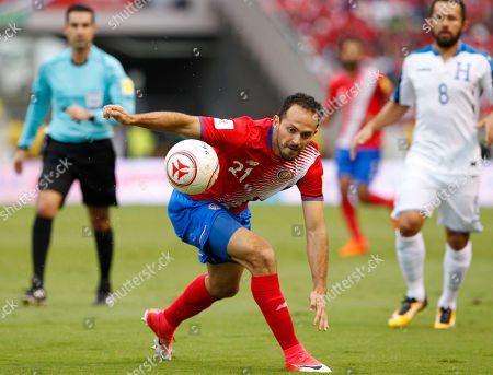 Costa Rica's Christian Bolanos, center, controls the ball during a World Cup qualifying soccer match against Honduras, at the National Stadium in San Jose, Costa Rica