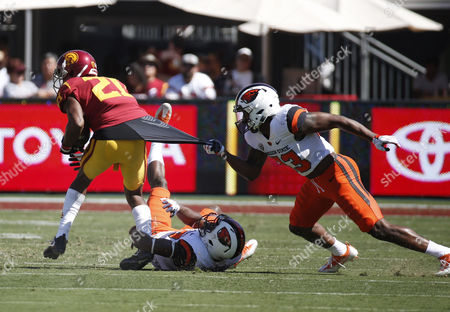 USC Trojans wide receiver Tyler Vaughns #21 is tackled by Oregon State Beavers safety Jalen Moore #33 during the football game between the USC Trojans and the Oregon State Beavers at the Los Angeles Coliseum in Los Angeles, California