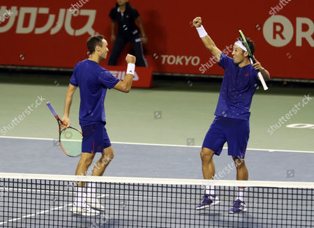 Japanese pair Yasutaka Uchiyama (R) and Ben McLachlan touch their fists as they won a point against Santiago Gonzalez of Mexico and Julio Peralta of Chile pair during the semi final of doubles of the Rakuten Japan Open tenni championships in Tokyo on Saturday, October 7 2017. Japanese pair won the match 7-5, 6-4.