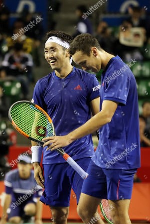 Stock Photo of Japanese pair Yasutaka Uchiyama (L) and Ben McLachlan celebrate their victory against Santiago Gonzalez of Mexico and Julio Peralta of Chile pair during the semi final of doubles of the Rakuten Japan Open tenni championships in Tokyo on Saturday, October 7 2017. Japanese pair won the match 7-5, 6-4.