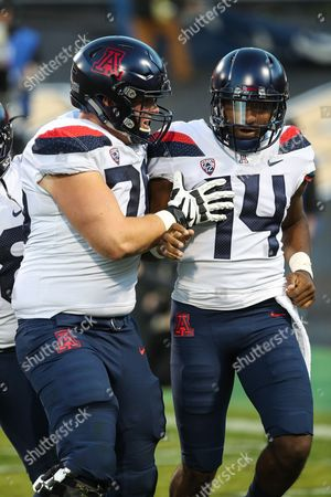Arizona QB Khalil Tate (14) and offensive lineman Cody Creason celebrate the first of Tate's four rushing touchdowns against Colorado. He set an FBS record for rushing yards for a QB as the Wildcats won, 45-42, in Boulder