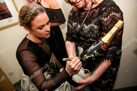 Kimberley Nixon signs a Tattinger champagne bottle