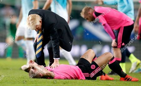 Scotland coach Gordon Strachan comforts Scotland's Leigh Griffiths, on the ground, after the World Cup Group F qualifying soccer match between Slovenia and Scotland, at the Stozice stadium in Ljubljana, Slovenia