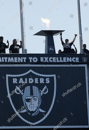 Former boxer Andre Ward waves after lighting a ceremonial torch in honor of former Oakland Raiders owner Al Davis before an NFL football game between the Raiders and the Baltimore Ravens in Oakland, Calif
