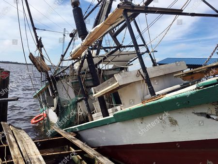 Stock Photo of A shrimp boat is sunk at its mooring along the Pascagoula River in Moss Point, Miss.,, after Hurricane Nate made landfall on Mississippi's Gulf Coast. David Nelson said the boat belongs to his father and will be repaired