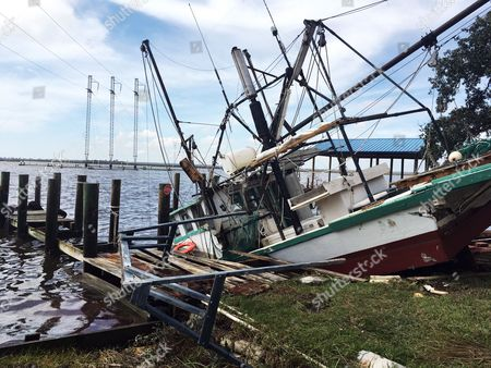 A shrimp boat is sunk at its mooring along the Pascagoula River in Moss Point, Miss.,, after Hurricane Nate made landfall on Mississippi's Gulf Coast. David Nelson said the boat belongs to his father and will be repaired