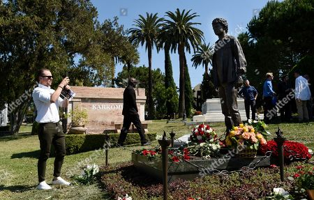 "Actor Simon Pegg takes a photo of a statue of the late actor Anton Yelchin during a life celebration and statue unveiling for Yelchin at Hollywood Forever Cemetery, in Los Angeles. Pegg and Yelchin were fellow cast members in the ""Star Trek"" film franchise. Yelchin died in June 2016 at the age of 27"
