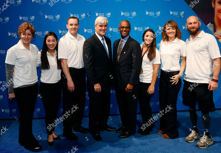 Liberty Mutual Insurance President and CEO, David H. Long, fourth left, and Liberty Mutual Insurance Chief Communications Officer, Paul Alexander, fourth right, are joined by Team USA curler, Tracy Sachtjen, left, two-time Olympic medalist, Michelle Kwan, second left, Team USA curler John Benton, third left, two-time gold medal gymnast, Aly Raisman, third right, three-time World Cup Snowboarding medalist, Amy Purdy, second right, and two-time U.S. Paralympics Alpine Skiing medalist, Heath Calhoun, right, at Liberty Mutual's Team USA One Year Out Celebration, on in Boston