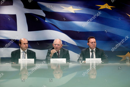 German Finance Minister Wolfgang Schaeuble, center, speaks as his Greek counterpart Yannis Stournaras, right, and Greek Development Minister Kostis Hatzidakis, left, sit alongside him during a news conference at the Greek Finance Ministry, in Athens. Wolfgang Schaeuble, the long-time German finance minister, is attending his final meeting of his peers in the 19-country eurozone on