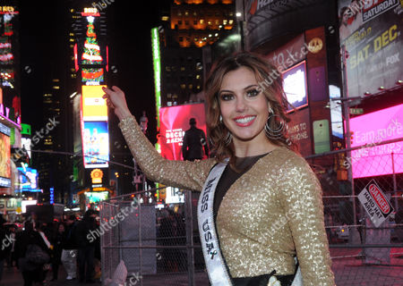 "IMAGE DISTRIBUTED FOR TOSHIBA - Erin Brady, Miss USA 2013, points to the 150-foot tall digital Christmas tree atop One Times Square on the Toshiba Vision and TDK screens, in New York. The tree will deliver high-tech holiday greetings to the ""Crossroads of the World,"" 24 hours a day, every 6 minutes, through January 13, 2014"