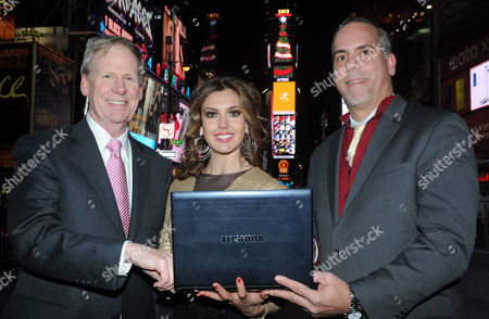 "IMAGE DISTRIBUTED FOR TOSHIBA - Frank Sweeney, left, of TDK, and Eddie Temistokle, right, of Toshiba, joined by Erin Brady, Miss USA 2013, unveil a 150-foot tall digital Christmas tree atop One Times Square on the Toshiba Vision and TDK screens, in New York. The tree will deliver high-tech holiday greetings to the ""Crossroads of the World,"" 24 hours a day, every 6 minutes, through January 13, 2014"