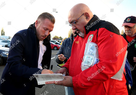 Ex Wales player Craig Bellamy sides autographs before the match.