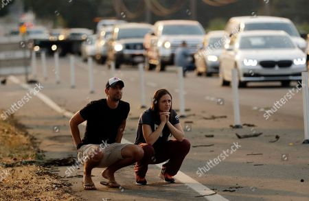 Drew Casey, Lauren Foster. Drew Casey, left, and his fiancee Lauren Foster watch a wildfire from a road closure, in Napa, Calif