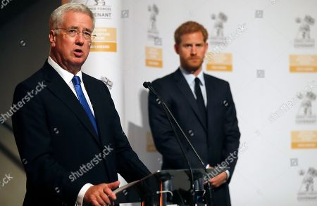 Britain's Prince Harry and Secretary of State for Defense Michael Fallon, left, present the Employer Recognition Scheme Gold Awards at the Imperial War Museum in London, . Prince Harry alongside the Secretary of State for Defense Michael Fallon presents the award to organizations from across the UK who have supported members of the Armed Forces and their families by offering training, work placements and employment. The Employer Recognition Scheme (ERS) was launched in 2014 to recognize employer support for the Defense and Armed Forces community