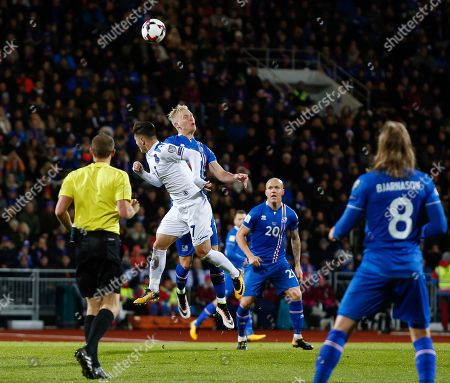 Iceland's Hordur Bjorgvin Magnusson, center, challenges Kosovo's Milot Rashica for the ball during the World Cup Group I qualifying soccer match between Iceland and Kosovo in Reykjavik, Iceland