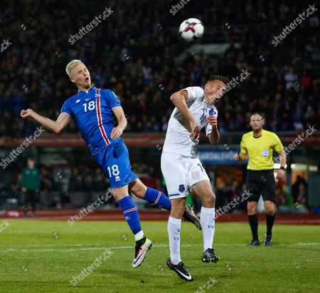 Iceland's Hordur Bjorgvin Magnusson, right, goes for a header against Kosovo's Mergim Vojvoda, during the World Cup Group I qualifying soccer match between Iceland and Kosovo in Reykjavik, Iceland