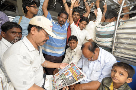 Commuters on a local train in South Mumbai survey with varying degrees of interest the Hindi Headlines which tell of a News of the World sting operation that allegedly trapped Rafiq Qureshi, father of Rubina Ali Qureshi, one of the young stars of 'Slumdog Millionare', into agreeing to sell his daughter to an Arab Sheikh for £200,000.