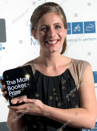 New Zealand author Eleanor Catton poses after being announced the winner of the Man Booker Prize for Fiction, holding her prize for the photographers, in central London, . Catton won the 50,000 pounds ($80,000) prize with her book 'The Luminaries
