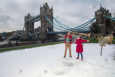 Actors Mark Rylance, left and Ruby Barnhill stand next to giant footprints imprinted in the snow, as they pose for photographers during a photo call for the film, The BFG, at Potters Field by Tower Bridge in London