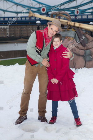 Actors Mark Rylance, left and Ruby Barnhill stand next to giant footprints imprinted in the snow, as they pose for photographers during a photo call of the film, The BFG, at Potters Field by Tower Bridge in London