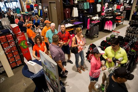Fans wait in line to meet golf commentator David Feherty at the new Golf Galaxy at the Shoppes at Parkwest in Katy, TX as part of the retailer's grand opening celebration on