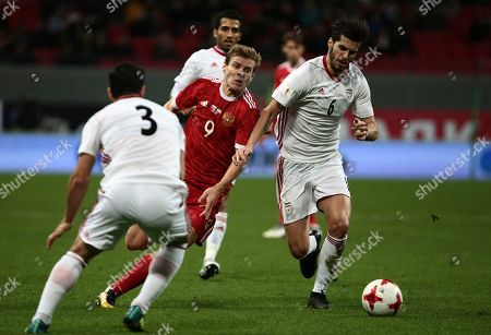 Saeid Ezatolahi, Ehsan Hajsafi, Alexander Kokorin. Iran's Saeid Ezatolahi, right, Ehsan Hajsafi, left, and Russia's Alexander Kokorin compete for the ball, during the friendly soccer match between Russia and Iran, in Kazan, Russia