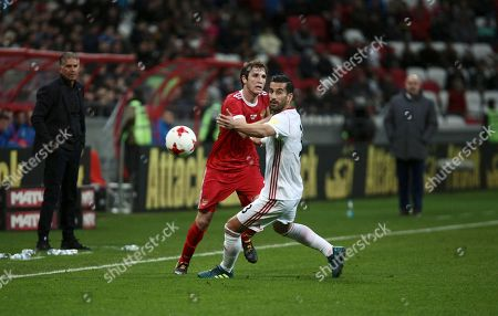 Ehsan Hajsafi, Mario Fernandes. Iran's Ehsan Hajsafi, right, and Russia's Mario Fernandes struggle for the ball during the friendly soccer match between Russia and Iran, in Kazan, Russia, on