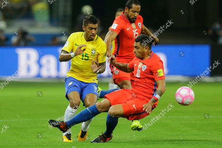 XWCUPSOUTHX. Brazil's Paulinho fights for the ball with Chile's Gonzalo Jara, right, during a World Cup qualifying soccer match in Sao Paulo, Brazil