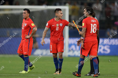 Chile's Eduardo Vargas, center, talks with lineman, as teammates Esteban Paredes, left, and Gonzalo Jara walk on the pitch after Brazil beat Chile 3-0, during a World Cup qualifying soccer match in Sao Paulo, Brazil