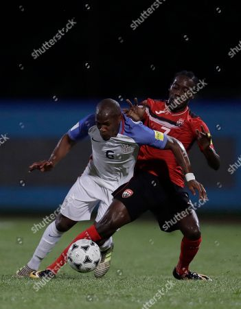 United States' Darlington Nagbe, left, and Trinidad and Tobago's Nathan Lewis, fight for the ball during a 2018 World Cup qualifying soccer match in Couva, Trinidad