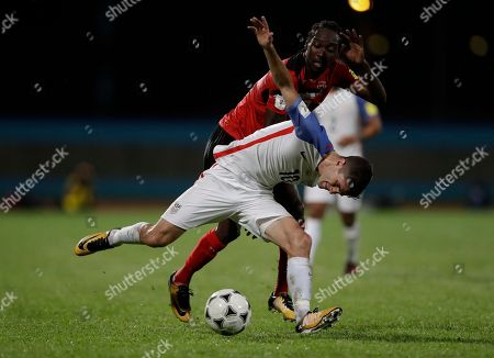 United States' Christian Pulisic, front, fights for control of the ball with Trinidad and Tobago's Nathan Lewis during a 2018 World Cup qualifying soccer match in Couva, Trinidad